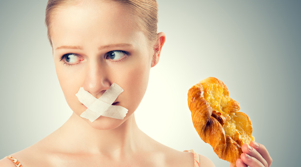 diet concept. woman mouth sealed with duct tape dreaming of biscuits and buns.